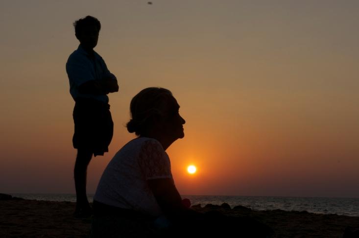 een oude vrouw geniet met haar zon op het strand van de ondergaande zon, een passend beeld bij het werk van Medi-Aid.